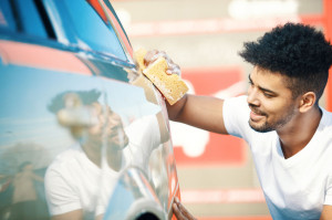 78028246 - young handsome man is washing car outdoor.