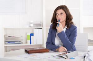 28339222 - portrait: unhappy older pensive business woman sitting at desk.