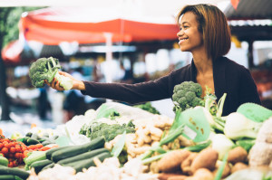 28471654 - young woman buying vegetables at farmers market
