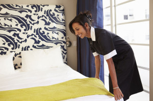 33546390 - maid tidying hotel room and making bed