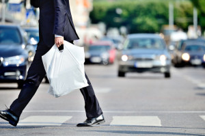 39294585 - man in suit with plastic bag crossing street