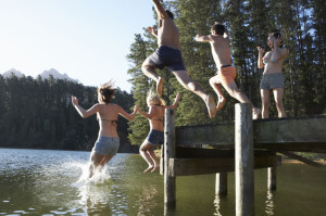 42249672 - group of young people jumping from jetty into lake