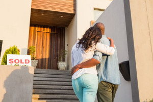 48190402 - back view of couple with arms above after buying house
