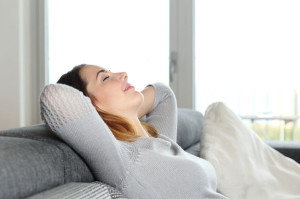 31105719 - happy relaxed woman resting on a couch at home with arms in the head