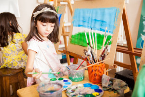 45584525 - cute girl mixing some colors for her painting in art class at school