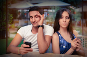 31627422 - secretive couple with smart phones in their hands