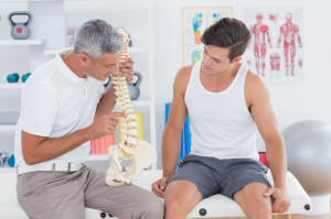 38333309 - doctor showing anatomical spine to his patient in medical office