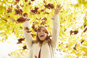 42270012 - woman throwing autumn leaves into the air