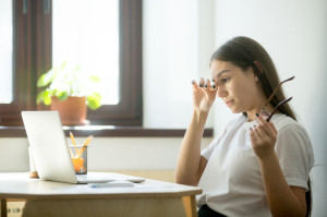 Tired businesswoman holding glasses and rubbing eyes in home off