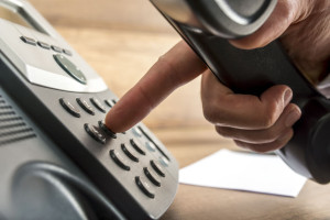 Closeup of male hand dialing a telephone number on black landlin