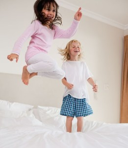 11686097 - portrait of playful siblings jumping on a bed