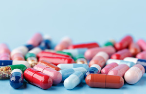 Heap of various pills on color background