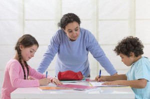 Woman helping kids with homework