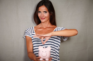 Happy woman holding a piggy bank with savings