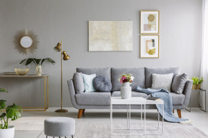 Real photo of a grey sofa with cushions and blanket standing in