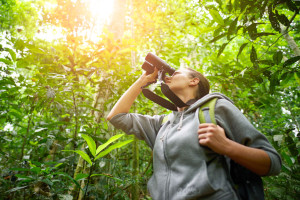 Young female hiker watching through binoculars wild birds in the