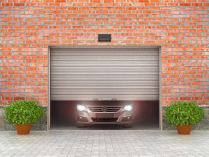 Garage concept. Garage doors are opened, and behind them is a ca