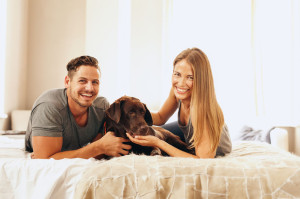 Young couple lying on the bed with their dog