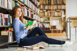 happy student girl reading book in library