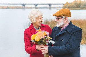 happy senior couple with bouquet