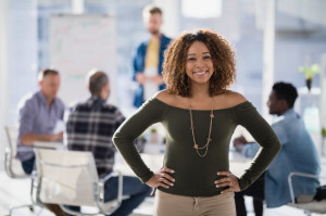 Female executive standing with hands on hip in the office