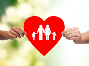 closeup of hands holding red heart with family