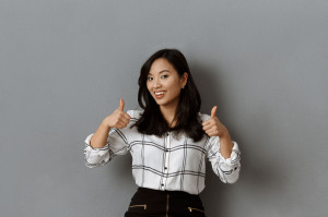 portrait of smiling asian businesswoman showing thumbs up against grey wall