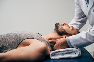 chiropractor massaging neck of handsome man lying on Massage Table on grey