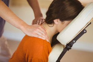 Young woman getting massage in chair in therapy room