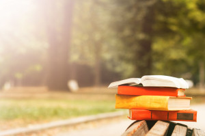 Stack of hardback books and Open book lying on bench at sunset park against blurred nature backdrop. Copy space, back to school. Education background.