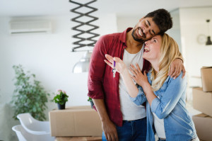 Young couple unpacking cardboard boxes at new home moving in concept