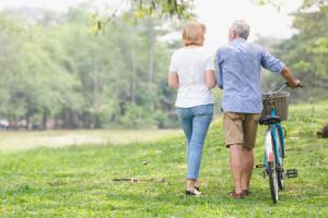 96079146 - senior couple walking their bike along happily talking happily.