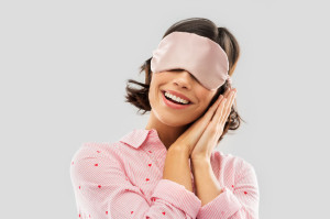 happy young woman in pajama and eye sleeping mask