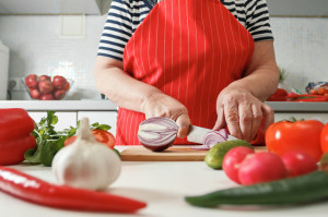 Senior woman cooking at home in the kitchen, cutting onions on a