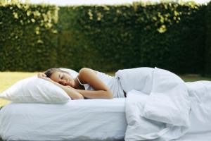 Girl sleeping on matress on grass
