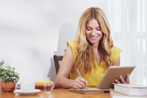 Smiling businesswoman writing in planner